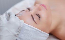 El cosmetologist del doctor hace el procedimiento facial de las inyecciones que rejuvenece para apretar y alisar arrugas imagen de archivo libre de regalías