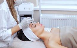 El cosmetologist del doctor hace el procedimiento facial de las inyecciones que rejuvenece para apretar y alisar arrugas foto de archivo