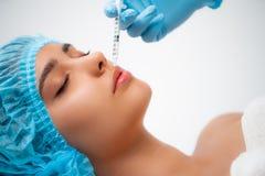 El cosmetologist del doctor hace el procedimiento facial de las inyecciones que rejuvenece para apretar y alisar arrugas en imagen de archivo