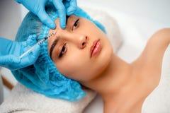 El cosmetologist del doctor hace el procedimiento facial de las inyecciones que rejuvenece para apretar y alisar arrugas en fotos de archivo