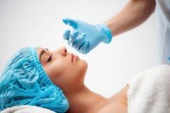 El cosmetologist del doctor hace el procedimiento facial de las inyecciones que rejuvenece para apretar y alisar arrugas en imagen de archivo libre de regalías