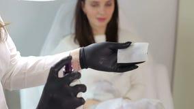 El cosmetologist en guantes negros salpica una solución estéril en una servilleta metrajes