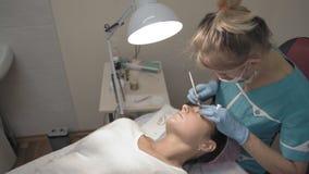 El Cosmetologist femenino en guantes hace la corrección de la ceja a su cliente almacen de metraje de vídeo