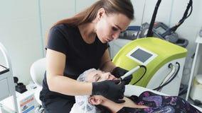El Cosmetologist hace el procedimiento de peladura hidráulico, aparato médico móvil a lo largo de la cara de la mujer en saló metrajes