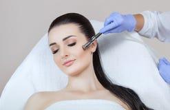 El cosmetologist hace el procedimiento Microdermabrasion de la piel facial de una mujer hermosa, joven en un salón de belleza fotografía de archivo