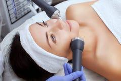 El cosmetologist hace el procedimiento una limpieza ultrasónica de la piel facial de una mujer hermosa, joven en un salón de bell foto de archivo libre de regalías