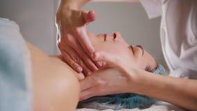 El Cosmetologist hace un masaje especial del cuello a su cliente para la elevación de la piel almacen de video