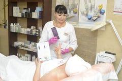 El cosmetologist ofrece los cosméticos del cliente, Ucrania, pueblo de Polyana, diciembre de 2018 fotografía de archivo