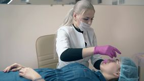 El Cosmetologist pone la hoja en la frente del cliente que tat?a en sal?n almacen de video