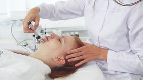 El Cosmetologist utiliza el iontophoresis para la cara del ` s del cliente foto de archivo
