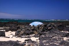 EL Cotillo - Faro del Toston: Guarda-chuva azul isolado entre rochas vulcânicas pretas na praia com horizonte Fuerteventura norte foto de stock