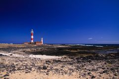 El Cotillo - Faro del Toston: View over dunes and rocky ground on red and white striped lighthouse in north of Fuerteventura. Iew over dunes and rocky ground on stock image