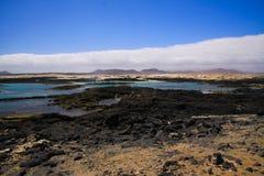 EL Cotillo - Faro del Toston: Vista panoramica sulla linea costiera approssimativa rocciosa con le lagune e gli stagni naturali n immagini stock