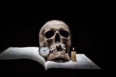 El cráneo humano en el libro abierto viejo con la vela ardiente y el vintage registran en fondo negro bajo haz de luz Foto de archivo