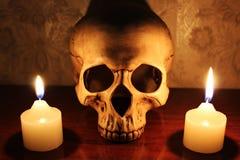 El cráneo y velas de luces Foto de archivo