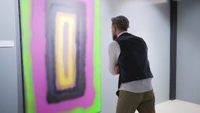 El crítico del arte está viendo el trabajo del pintor abstracto joven en la exposición almacen de metraje de vídeo