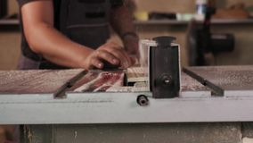 El craftman est? trabajando en la m?quina el?ctrica de la sierra Aserrar a un tablero de madera grande almacen de metraje de vídeo