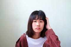 El cratching asiático de la mujer principal y pensamiento en algo Imagen de archivo