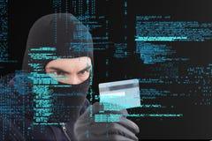 El criminal cibernético que lleva una capilla está sosteniendo una tarjeta de crédito contra fondo digital de la lluvia de la mat Fotografía de archivo