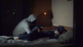 El criminal del ladrón en una máscara roba en la casa en donde duerme la muchacha almacen de video