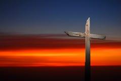 El cristiano cruza encima el fondo oscuro de la puesta del sol Fotografía de archivo libre de regalías