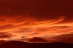 El cristiano cruza encima paisaje rojo del fondo de la puesta del sol Imagen de archivo