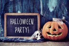 El cráneo, la calabaza y el texto Halloween van de fiesta en una pizarra Foto de archivo