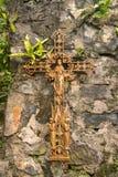 El crucifijo oxidado viejo puso a la pared de piedra vieja Imágenes de archivo libres de regalías
