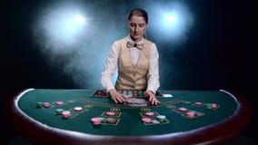 El crupié de la muchacha en un casino mezcla tarjetas en fondo ahumado negro con los proyectores Cámara lenta metrajes