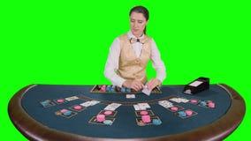 El crupié de sexo femenino del casino que se coloca en la tabla toma las tarjetas del portatarjetas para el juego en póker Pantal almacen de metraje de vídeo