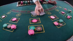 El crupié del casino distribuye las tarjetas bajo la forma de arco en la sobremesa del póker Cámara lenta Cierre para arriba almacen de metraje de vídeo