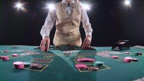 El crupié del casino distribuye para las tarjetas del póker tres de la tabla es el fracaso Fondo negro Luz brillante Cámara lenta metrajes