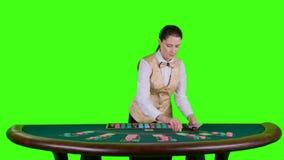 El crupié del casino en una camisa blanca distribuye para las tarjetas del póker tres de la tabla es el fracaso Pantalla verde Cá almacen de metraje de vídeo