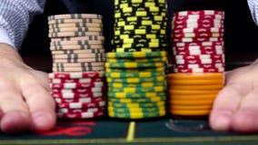 El crupié mueve microprocesadores en la tabla en el casino, negro, vista delantera metrajes