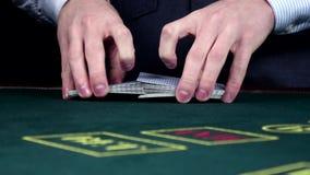 El crupié que mezcla tarjetas, las muestra en el casino, cámara lenta metrajes