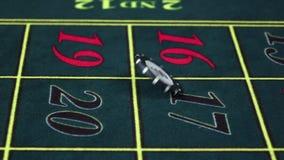 El crupié tuerce el microprocesador en la tabla verde en el casino, cámara lenta metrajes