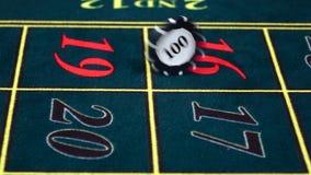 El crupié tuerce el microprocesador en la tabla verde en el casino, vista delantera metrajes