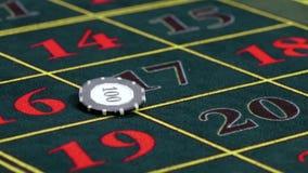 El crupié tuerce un microprocesador usual en la tabla verde en el casino almacen de metraje de vídeo