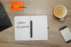 El cuaderno abierto con el ` del texto APRENDE el ` de la ECONOMÍA y una taza de café en fondo de madera Imágenes de archivo libres de regalías