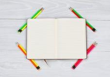 El cuaderno abierto con nuevamente afila los lápices en la mesa blanca Foto de archivo