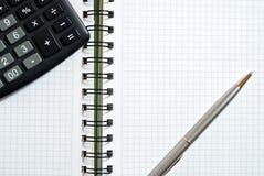 El cuaderno, ballpen y calculadora Fotos de archivo