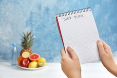 El cuaderno de la tenencia de la mujer con las palabras ADIETA PLAN cerca de las frutas en fondo del color fotos de archivo