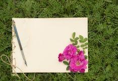 El cuaderno de notas hecho a mano con las flores y las hojas de salvaje subió Foto de archivo