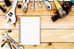 El cuaderno del papel en blanco con las herramientas prácticas cae en fondo de madera Imagenes de archivo