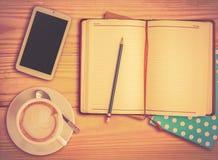 El cuaderno, el lápiz, el teléfono elegante y la taza de café con vinage filtran Foto de archivo libre de regalías