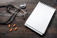 El cuaderno, el phonendoscope y las píldoras en la visión de escritorio de madera oscura llaman una mofa del doctor Fotografía de archivo libre de regalías