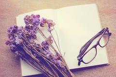 El cuaderno en blanco y el statice secado florece con las lentes, retras Foto de archivo libre de regalías