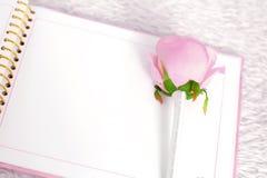 El cuaderno en blanco y subió en una alfombra blanca Fotos de archivo