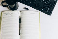 El cuaderno en la tabla con la pluma y la taza imagen de archivo libre de regalías
