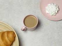 El cuaderno, el lápiz y los sacapuntas de madera, la taza de café, la melcocha en la tabla del granito y el piso blanco imagenes de archivo
